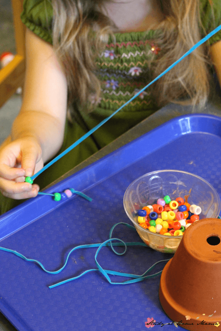 Lacing beads onto leather string as part of making a homemade wind chime with kids