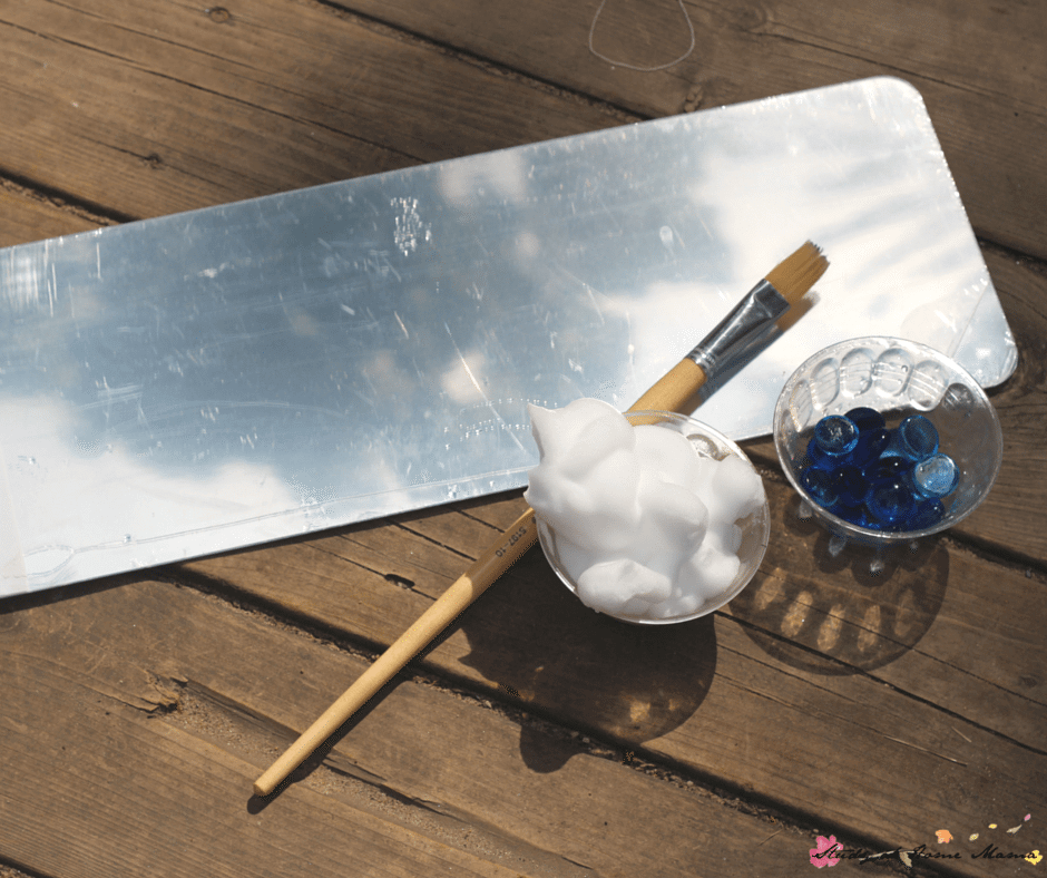 Materials Needed for Cloud Painting Sensory Activities for Children: Unbreakable mirror, shaving cream, and glass gems