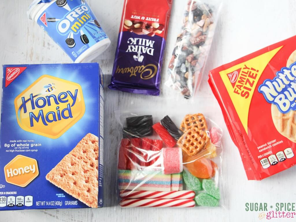 Ingredients for making your own edible fairy house with cookies and candy. How to make cookie fairy house