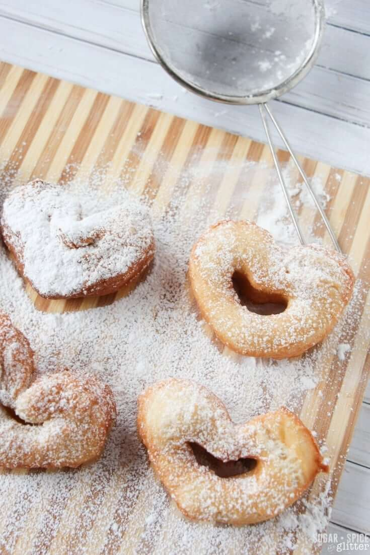 An easy and authentic recipe for heart-shaped beignet donuts, a New Orleans specialty perfect for Mardi Gras or enjoying with a Princess and the Frog movie night