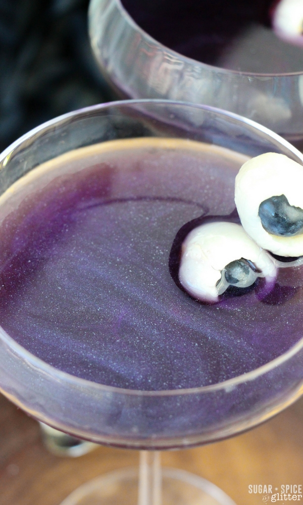 How mesmerizing is this shimmery night sky rum cocktail - a pretty and delicious Halloween cocktail with fruit eyeballs - take out the garnish for a night sky cocktail that you can serve all year round