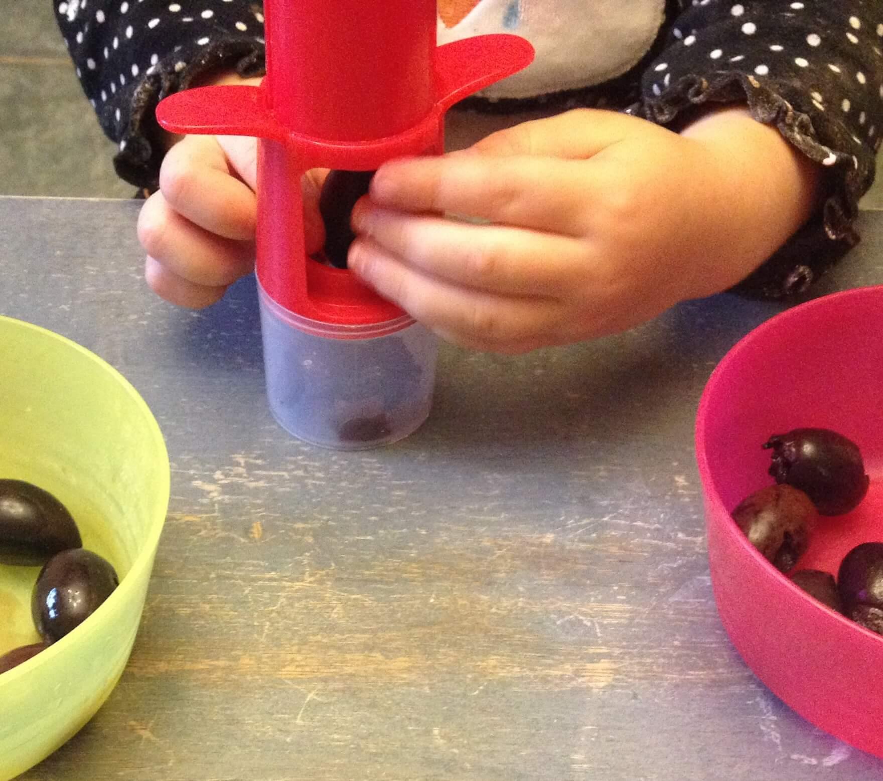 Fine motor kitchen activity: olive pitting
