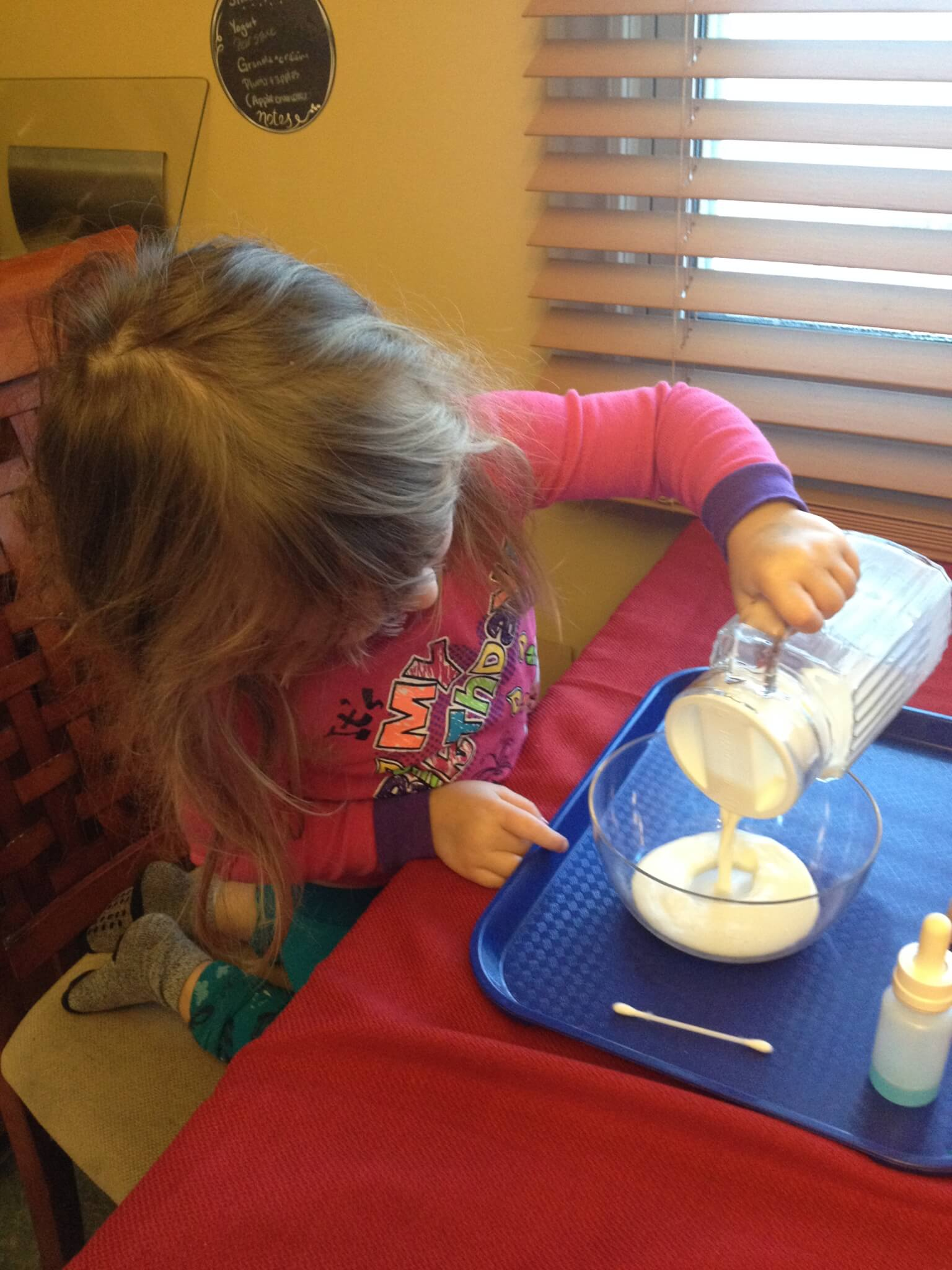 milk and dish soap experiment: pouring milk is a montessori practical life skill used in this fun science experiment