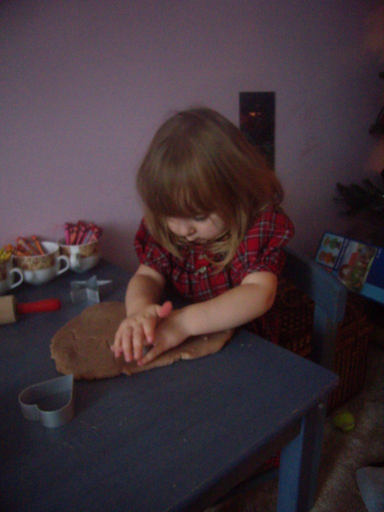 Ella making gingerbread play dough ornaments