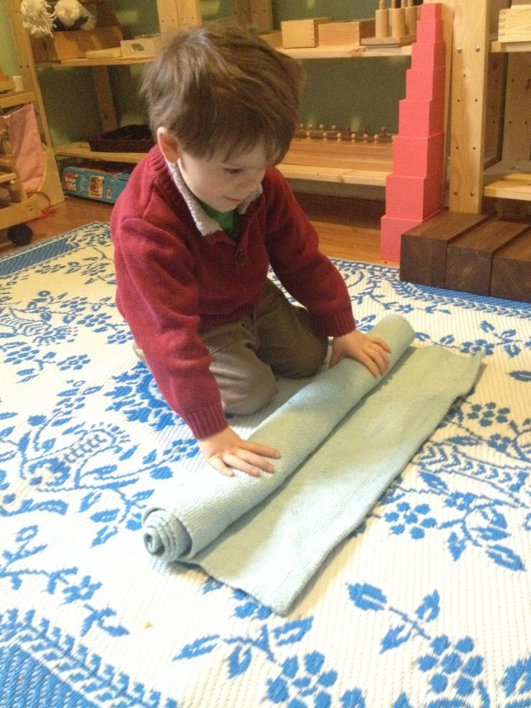 Child unrolling a work mat - Montessori presentation and lesson at Sugar, Spice and Glitter