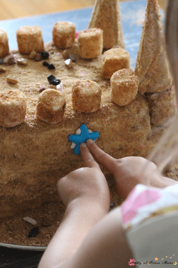 Chocolate rocks and icing starfish make the perfect toppings for this homemade sandcastle cake - perfect for a beach themed party