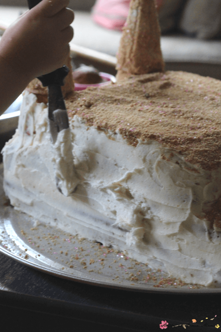 Homemade vanilla buttercream helps the edible sand stick to this homemade sandcastle cake