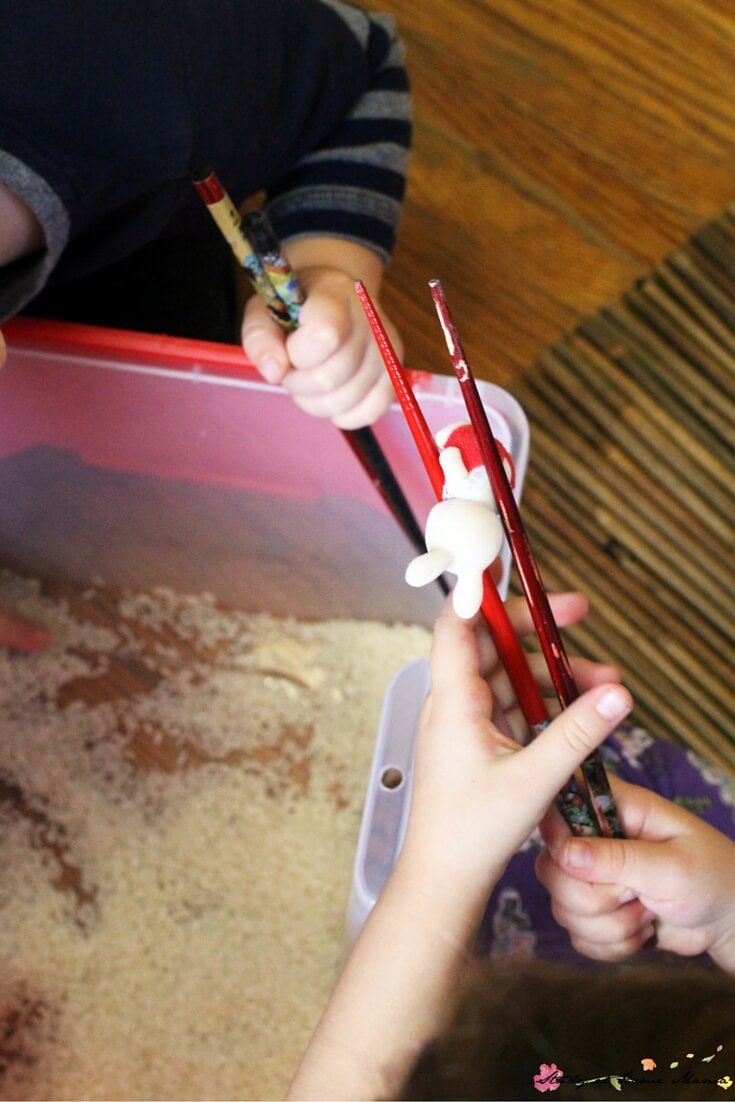 Learning how to pick up items with chopsticks, using a fun sensory bin invitation
