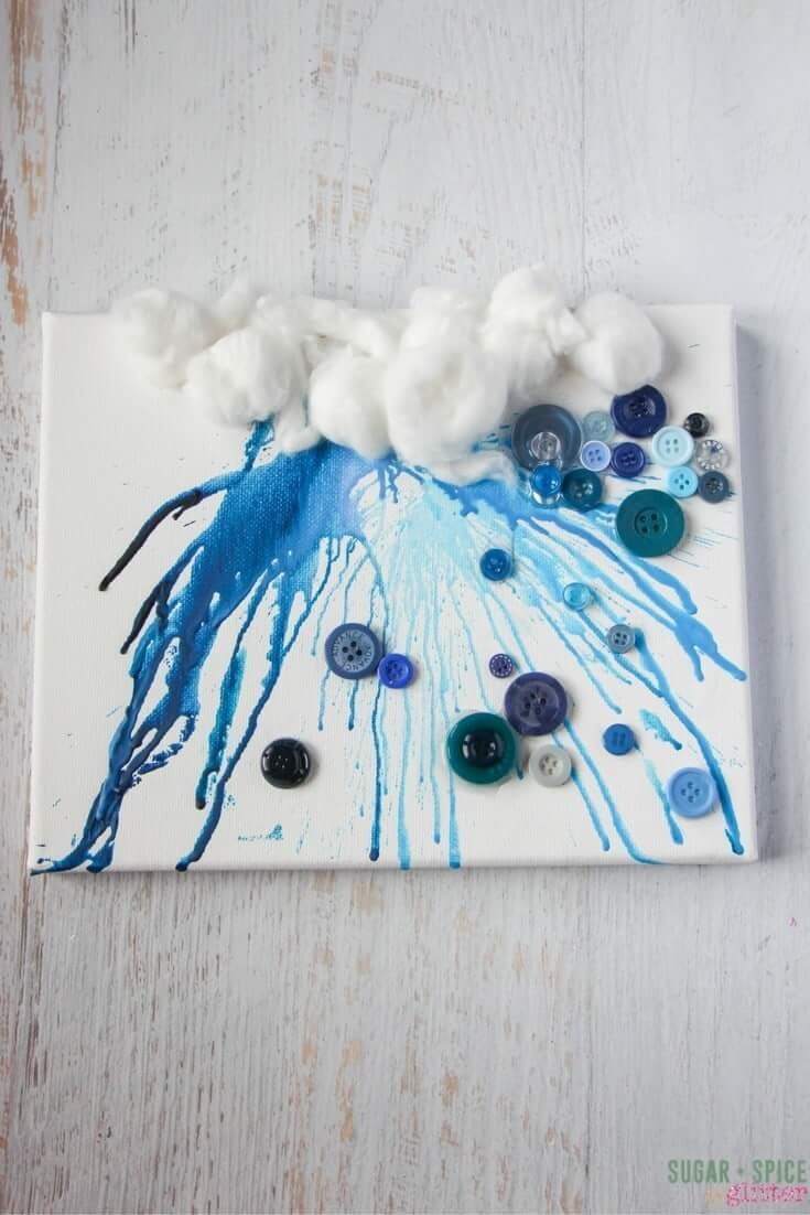 The perfect process art project for a rainy day, this crayon drip cloud with button rain drops is such a cute craft that kids will love making - from melting the crayons to decorating the canvas with cotton and buttons