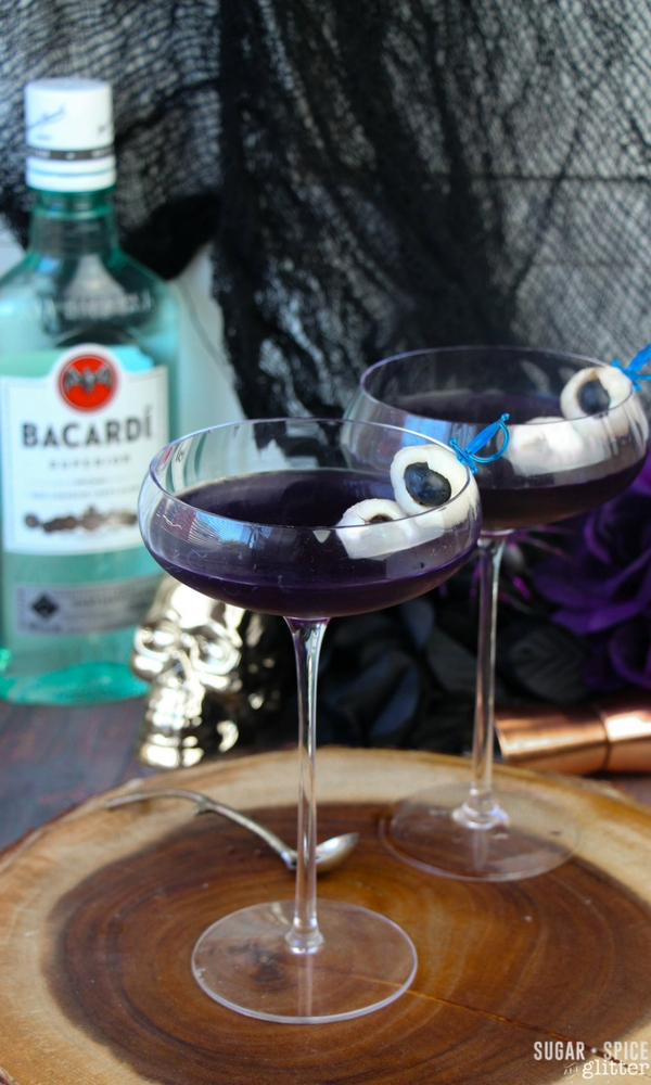 A spooky Halloween rum cocktail with edible fruit eyeballs skewered for a ghoulish touch