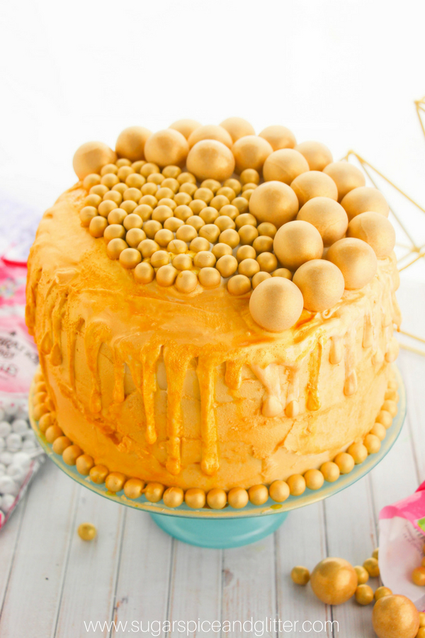 A fun DIY Gold Birthday Cake with a dramatic drip effect. The edible gold gumballs add a bubbly champagne effect to this pretty celebration cake