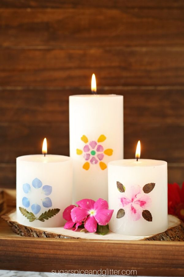 A gorgeous handmade gift for a birthday, Mother's Day or to display pressed flowers from a vacation, this easy candle craft uses pillar candles and fresh picked flowers for a beautiful piece of homemade decor