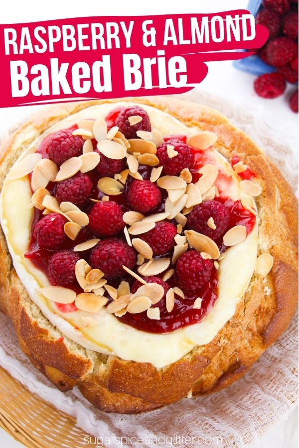 A decadent baked brie recipe topped with raspberry jam, fresh raspberries and toasted almonds, baked right in a sourdough bread bowl. This cheesy appetizer is perfect for any special occasion: anniversaries, Valentine's Day, Mother's day, or a special night with the girls.