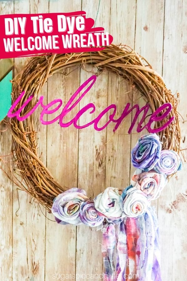 How gorgeous is this DIY Tie Dye Welcome Wreath?! A fun boho-chic, new country craft that brings some summer vibes to your entryway for less than $10 to make! You can also use old clothing to make the fabric roses and fringe, if desired